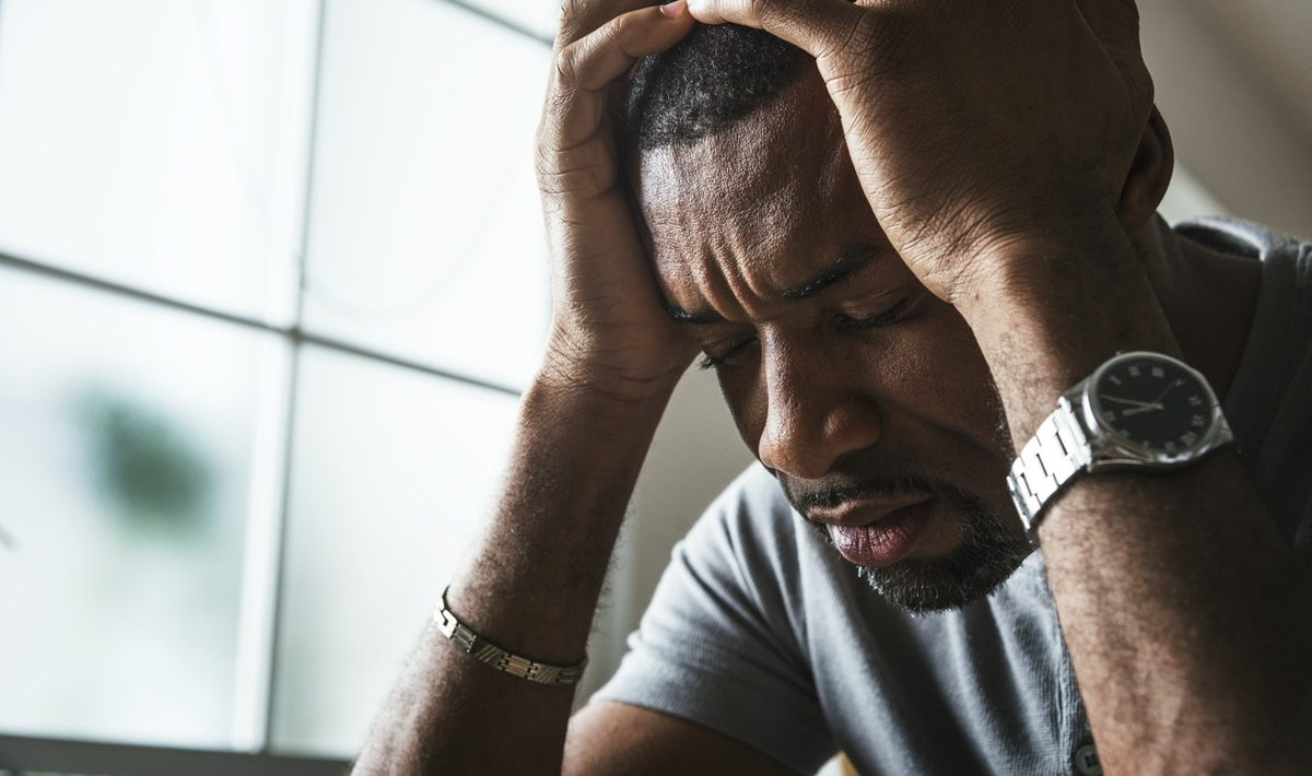 Signs you're sabotaging yourself -Black guy stressing and headache